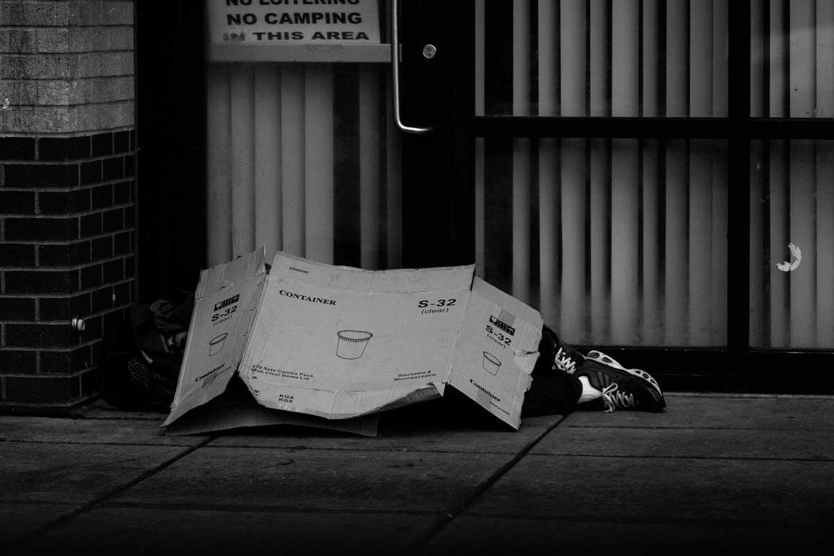 Man sleeping under cardbox box - B&W
